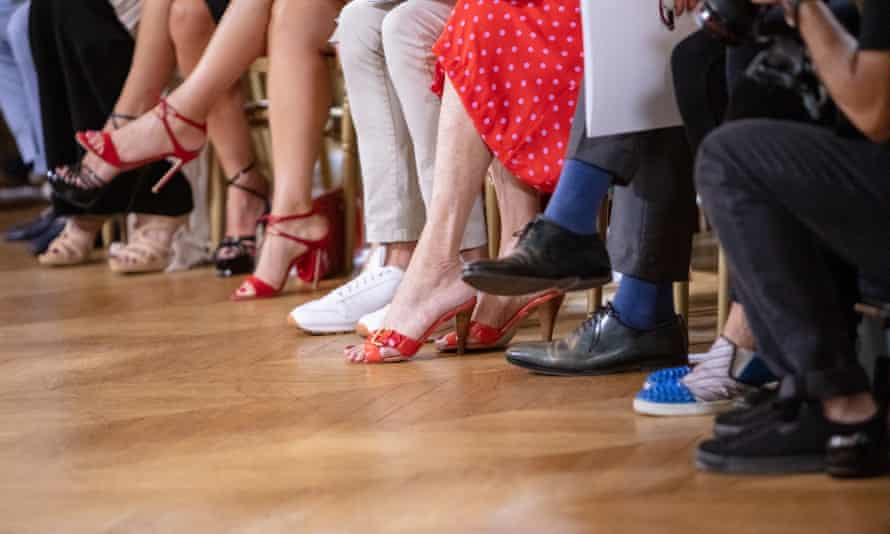A row of men and women in stylish shoes at a fashion show