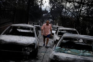 A man walks among burnt cars following a wildfire at the village of Mati