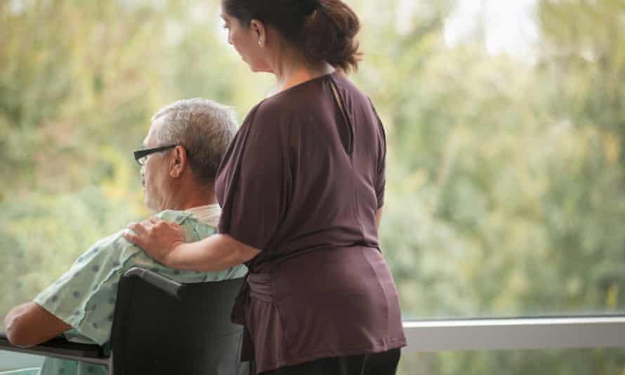 woman comforting man in wheelchair