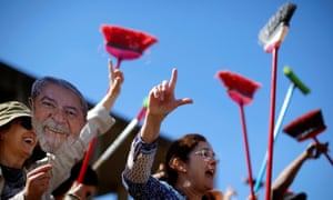 Demonstrators raise their brooms as they sweep outside the justice ministry headquarters during a protest against Sergio earlier this month.