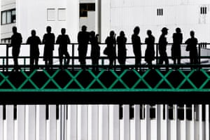 """Eiffel Bridge, by Jose Pessoa Neto, taken in Portugal: """"People were waiting for the street festival Senhora da Agonia, one of the biggest in Portugal. From the street, I saw these beautiful silhouettes, the bridge, the green crosses and the building behind in harmony."""""""