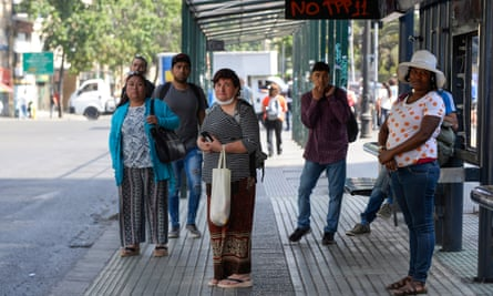 People wait at a bus stop during a national strike and general demonstration in Santiago, Chile, on 12 November.