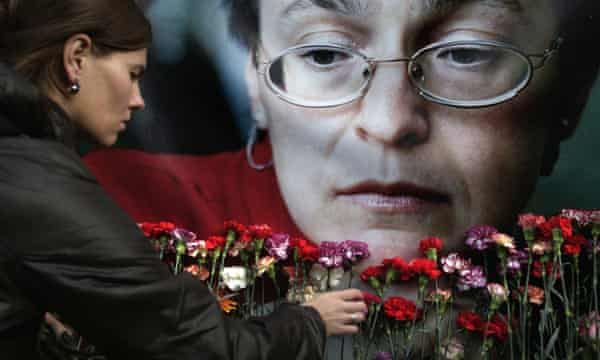 A woman places flowers before a portrait of the murdered Russian journalist Anna Politkovskaya in 2009.