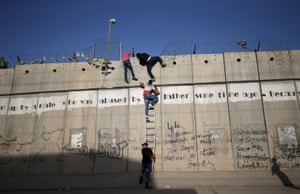 Palestinians, not permitted by Israeli security forces to cross into Jerusalem from the West Bank due to an age limit, climb over a section of the controversial Israeli barrier as they try to make their way to attend the first Friday prayer of Ramadan in Jerusalem's al-Aqsa mosque