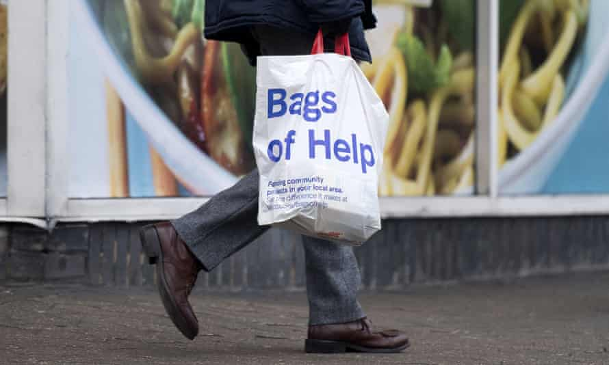 A person with a Tesco carrier bag