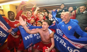 The Accrington Stanley players and coaching staff start the promotion celebrations in the dressing room.