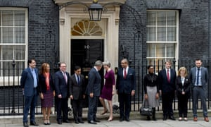 Theresa May heading back into No 10 after posing for a picture with her new Conservative party chairman Brandon Lewis (standing on May's right), James Cleverly, the new Conservative deputy chairman (standing on her left) and the party's new vice chairmen.