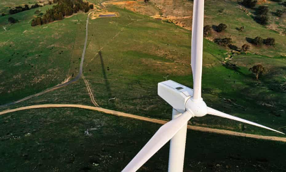 aerial view of wind turbine with green countryside below