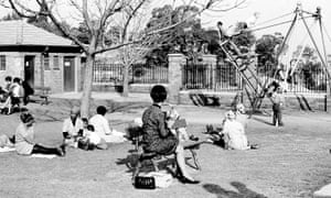 """White men and women sit on benches that are """"For Whites Only,"""" while black African women looking after white children sit on the ground at a park in central Johannesburg in 1965."""