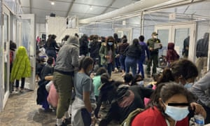 Migrants crowd a room with walls of plastic sheeting in Donna, Texas.