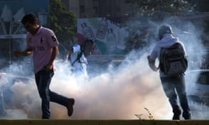 Venezuelans run away from tear gas during scuffles with security forces in Caracas.