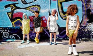 four children in simple cotton, bold-patterned clothing, standing in front of a wall of graffiti