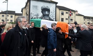 Sinn Féin president Gerry Adams (left) watches on as mourners carry Martin McGuinness's coffin past the murals at Free Derry Corner.