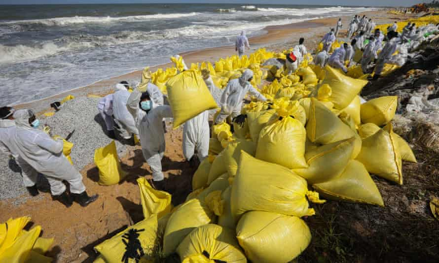 Sri Lankan navy personnel wearing cleanup gear on a beach with yellow sacks full of debris