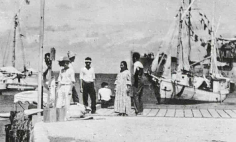 The woman said to resemble pilot Amelia Earhart is seen sitting on the dock in the centre of the picture.