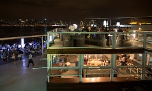 Diners sit on the terrace of the luxury Cais de Quatro restaurant overlooking the city skyline in the Angolan capital Luanda.