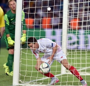 Sevilla's Kevin Gameiro picks the ball out the net after scoring his penalty.
