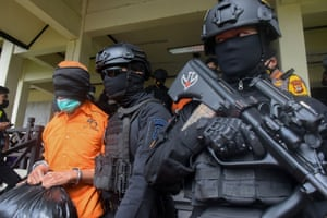 Makassar, Indonesia: Police escort one of a group of 19 terror suspects being transferred to Jakarta from Makassar, at the Sultan Hasanuddin airport