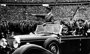 Adolf Hitler giving a nazi salute to a crowd of soldiers at a Nazi rally.