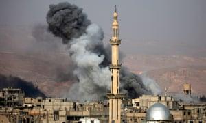 Smoke rises behind a minaret in Arbin, Syria
