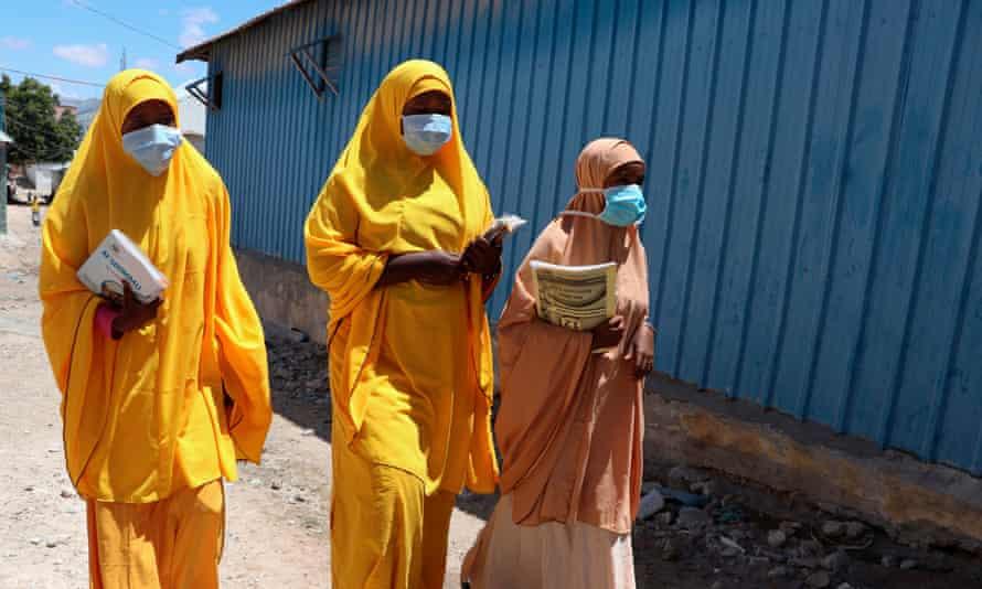 Students walk in a Mogadishu neighbourhood wearing face masks, Somalia