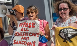 People shout against benefit cuts and sanctions at the protest outside Kentish Town Jobcentre, London
