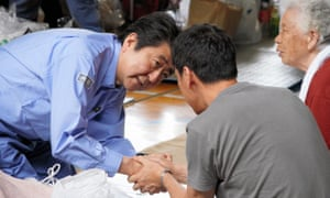 The Japanese prime minister, Shinzo Abe, left, talks with evacuees at in Kurashiki, Okayama prefecture.