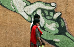 An Indian couple walks past a mural in Bangalore, India