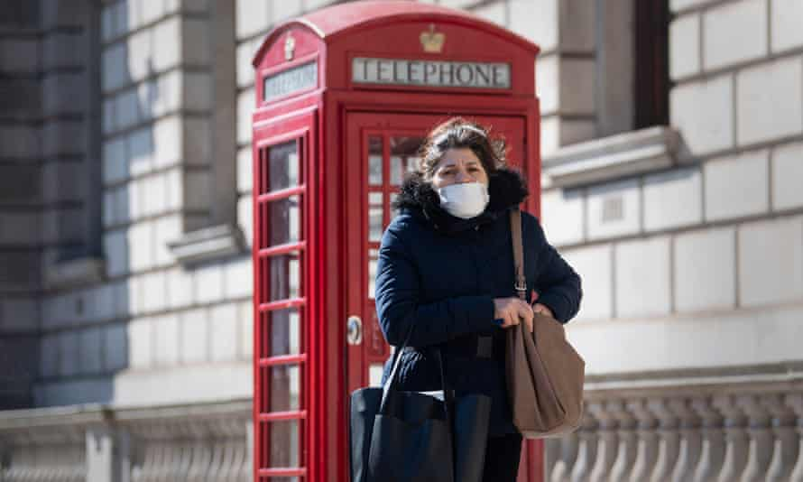 A woman wearing a protective face mask in central London