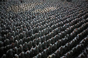 Iraq, Mid 2008, 1,215 American soldiers, airmen, marines (patch of lighter uniforms in top left corner) and seamen (patch of lighter uniforms in top center) pray before the pledge of enlistment on July 4, 2008, at a massive re-enlistment ceremony in Al Faw palace in Baghdad, Iraq on July 4, 2008. Gilbertson himself in the cauldron of the Iraq War (2003–2011) at a critical moment, with no end in sight. Wanting to vividly illustrate the impressive scale of the American effort, he has chosen here to show massed ranks of soldiers in a spectacle designed to boost morale – a kind of military Super Bowl.