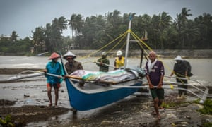 Fishermen carry a boat to higher ground in Baybay, eastern Samar, Philippines, during Typhoon Phanfone.