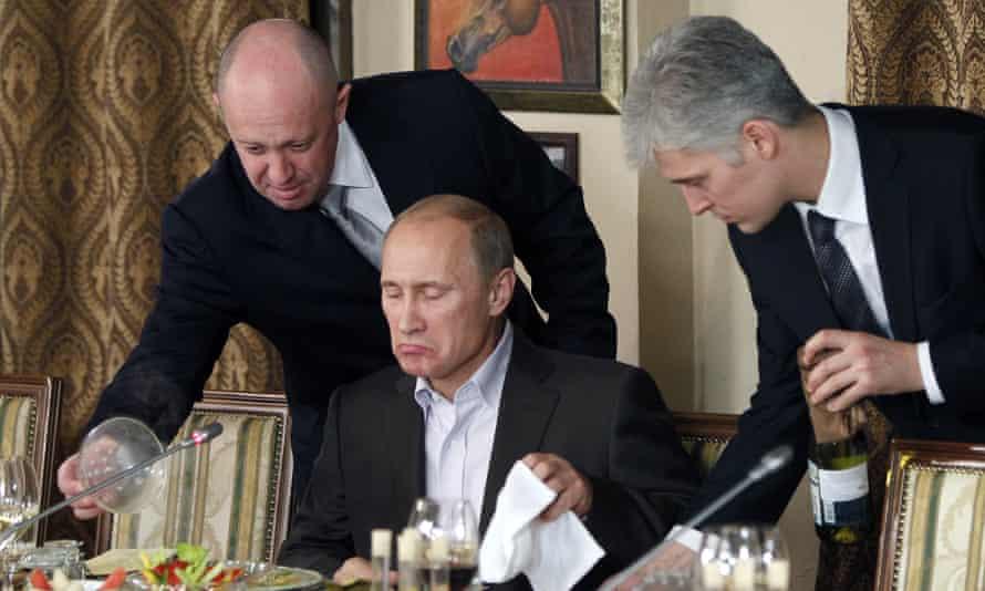 Yevgeny Prigozhin (left) serves food to Vladimir Putin at his restaurant in 2011.