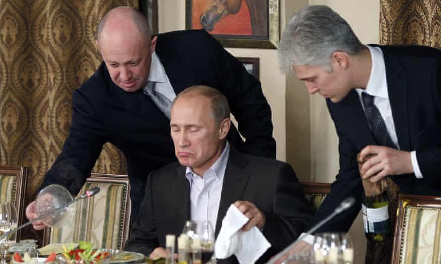 Yevgeny Prigozhin, left, serves food to Vladimir Putin at Prigozhin's restaurant outside Moscow in 2011.