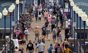 Few people wear masks as they walk on a pier in Oceanside, California, on Monday.