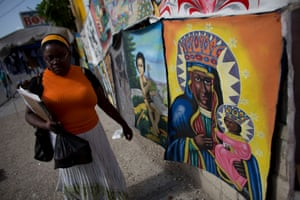 A woman walks past a painting depicting the voodoo spirit Erzulie Dantor, often depicted in a style derived from that of a Black Madonna.