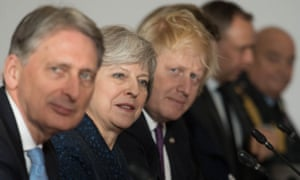 Philip Hammond, Theresa May and Boris Johnson look up during UK-France summit in Sandhurst.