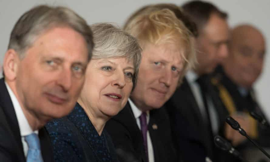 Philip Hammond, Theresa May and Boris Johnson look up during UK-France summit in Sandhurst.