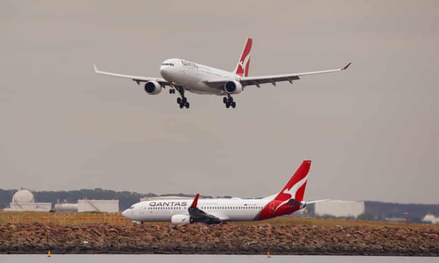 qantas plane flies over a grounded plane at Sydney airport
