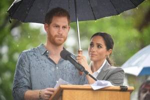 Prince Harry address the crowd as Meghan Duchess of Sussex holds an umbrella for him during a Dubbo community BBQ in Victoria Park