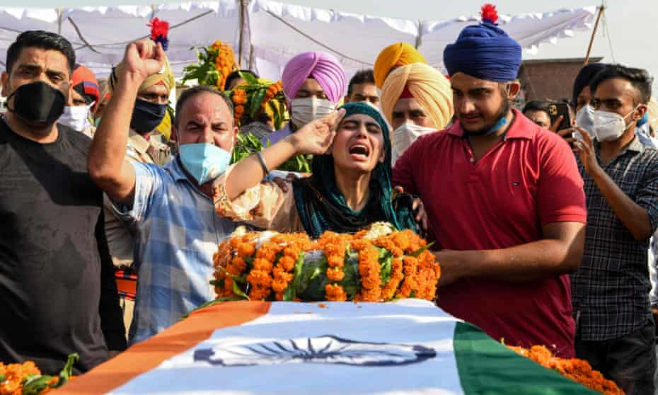 Sandeep Kaur and her brother Prabhjot Singh lay flowers on the coffin of their father, Satnam Singh, who was killed in the fight in the Galwan Valley.