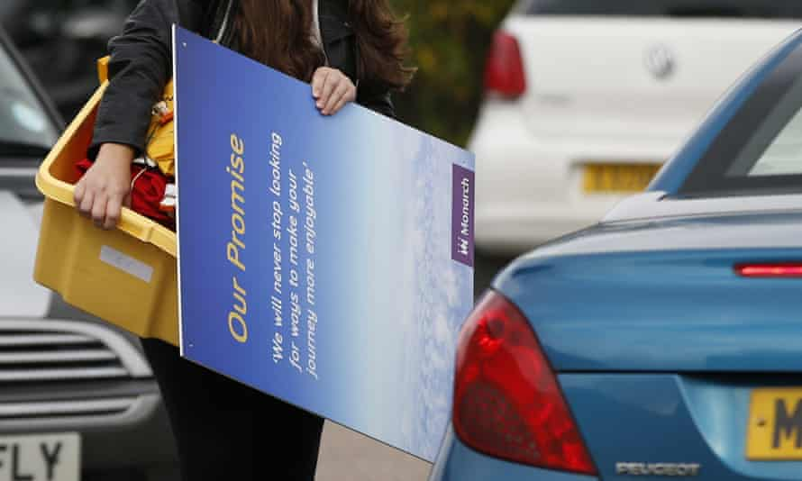 A member of Monarch Airlines cabin crew carries her personal belongings to her car at Luton