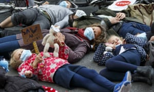 Parents and children stage a die-in protest against pollution in London.