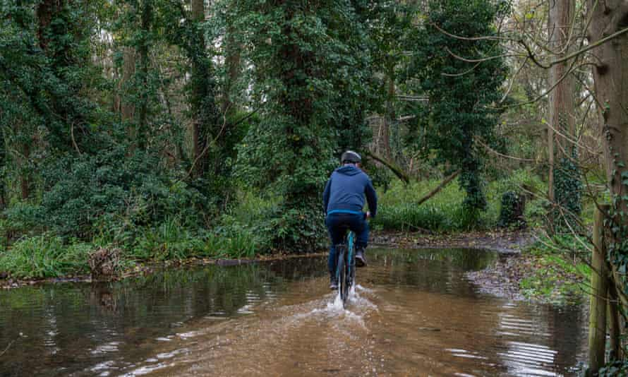 A cyclist struggles through a flooded trail after the chalk stream River Colne burst its banks in Buckinghamshire in November.