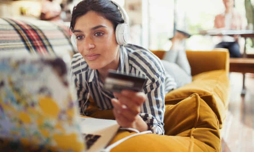 Young woman with credit card and headphones online shopping at laptop on living room sofa