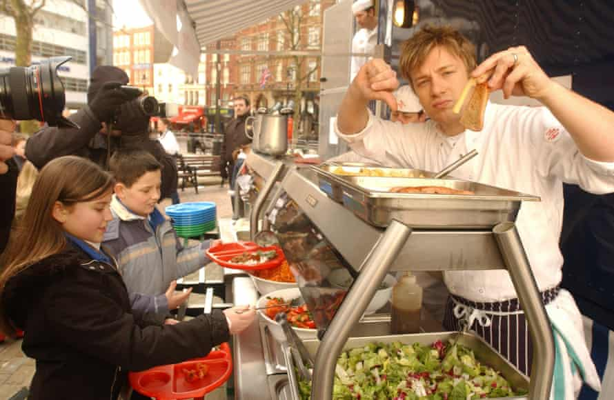 Serving up culinary opposition … Oliver gives the thumbs down to chips and fatty food as he serves up a healthy lunch at Ealdham primary school in London in 2005.