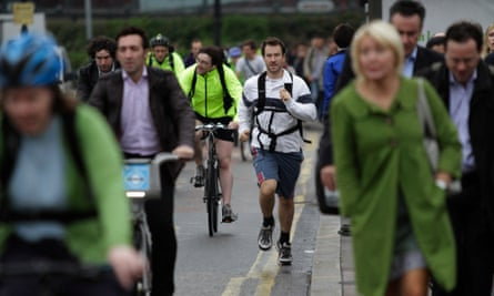Commuters walk, use bicycles and jog on a central London bridge
