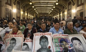 Family members hold posters that show images of their missing sons during a signing ceremony at the National Palace in Mexico City on Monday.