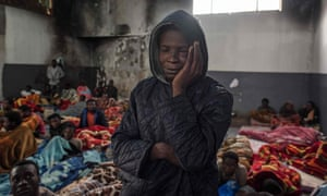 A migrant stands in a packed room at the Tariq al-Matar detention centre on the outskirts of the Libyan capital, Tripoli.