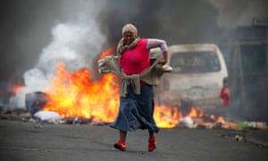 A terrified resident runs past burning barricades