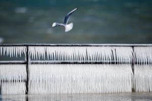 A seagull flies by an ice covered banister on the frozen shore of Lake Geneva during a windy winter day, in Coppet, Switzerland.
